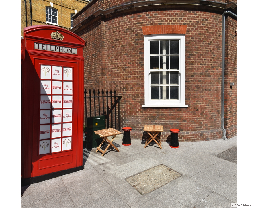 If you want a seat, two small tables (each with a stool) lurk behind the telephone box.