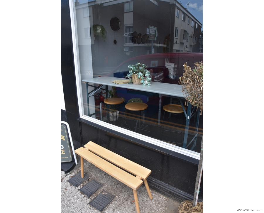 ... this bench in front of the window to the left of the door...