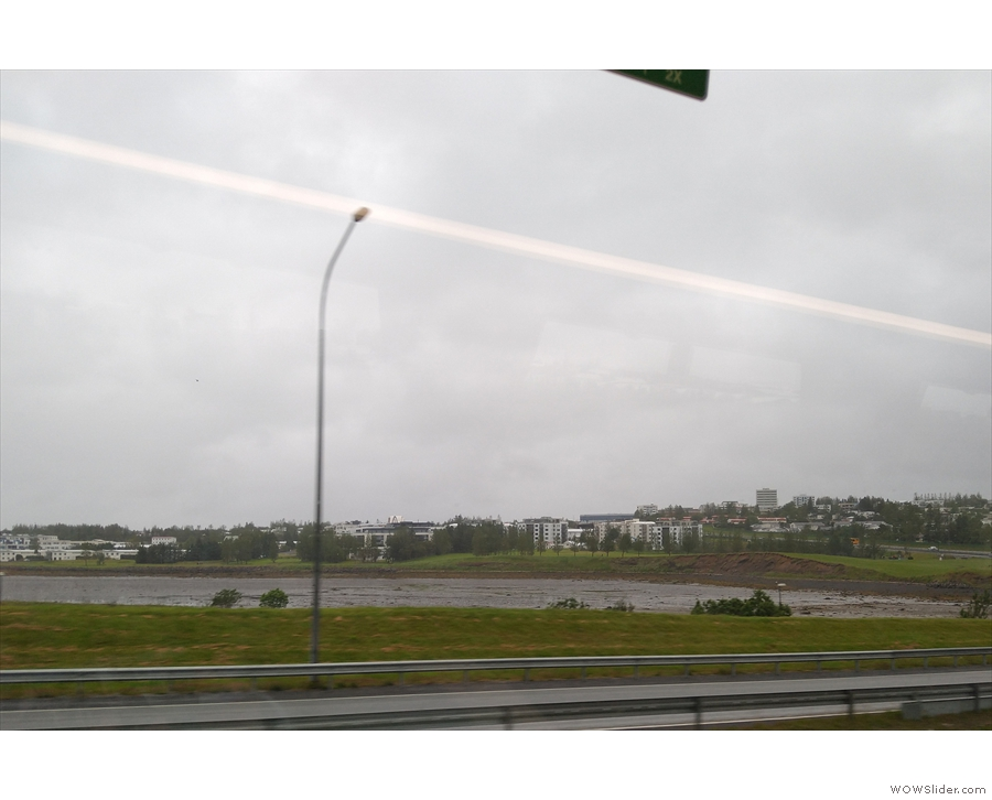 By now, the bus was approaching the southern outskirts of Reykjavik, before...