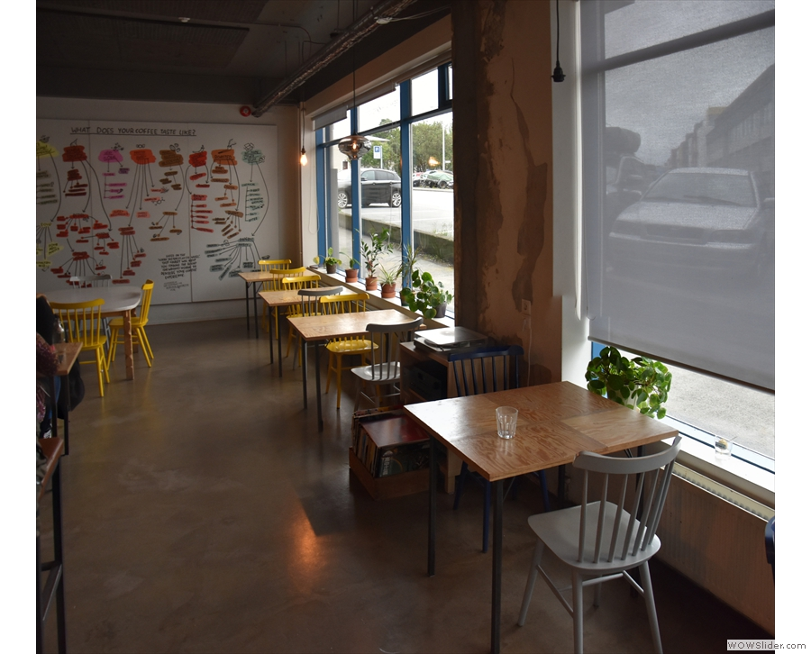 ... followed by a row of five two-person tables under the windows. There are two...