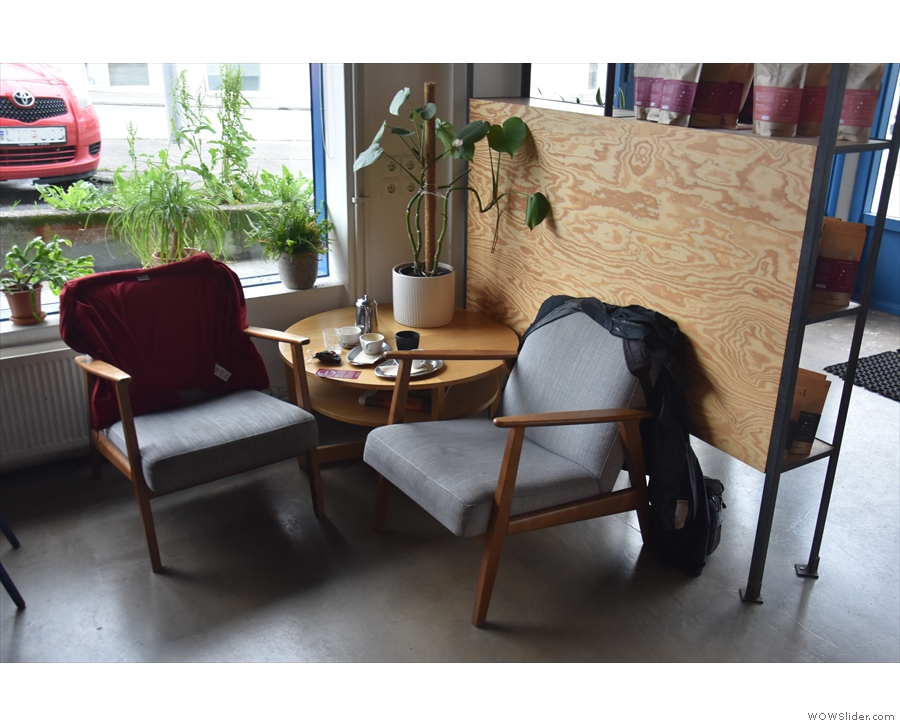 The seating starts, immediately beyond the retail shelves, with a pair of armchairs...