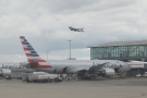 A British Airways A319 takes off over an American Airlines 777-200 waiting to go to JFK.