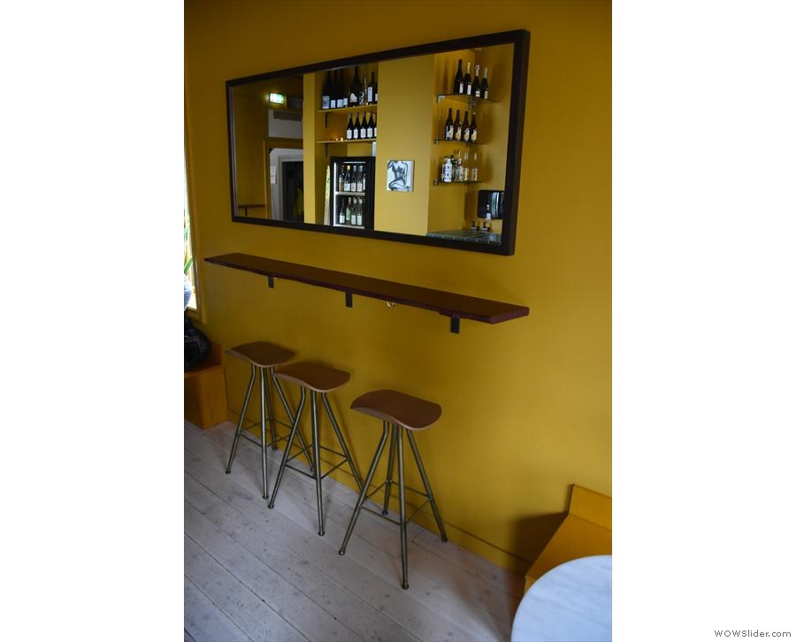 Matching that are three more stools at a narrow bar under a mirror.