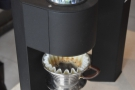... applying a pre-programmed series of pulses of water to the coffee...