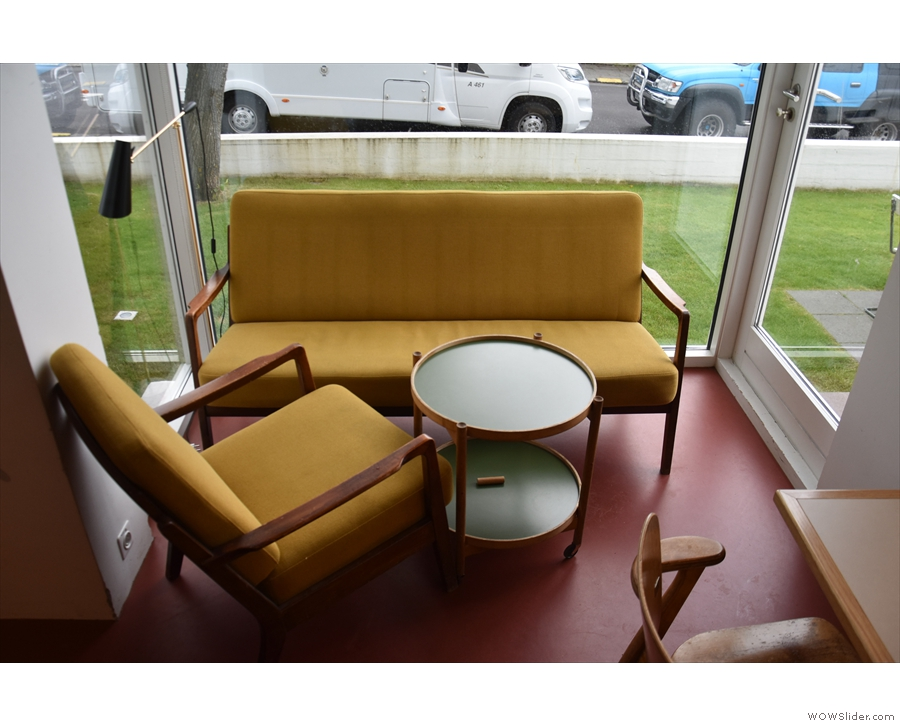 ... with this three-sided glass porch, occupied by a sofa and matching armchair.