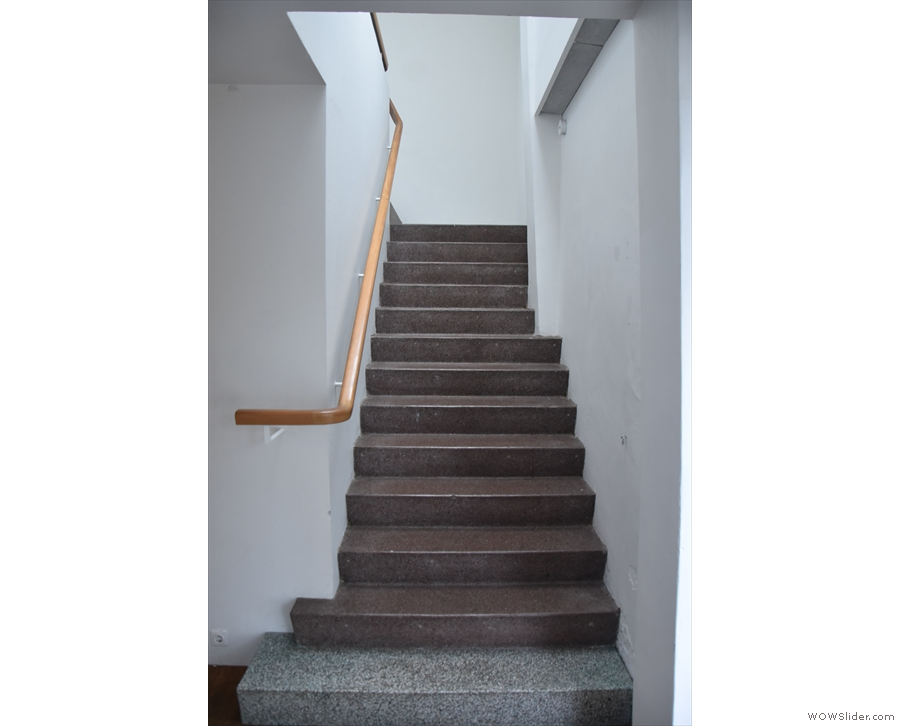 To the right is a flight of stairs leading to the upstairs gallery space.