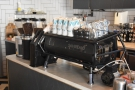 ... the Sanremo espresso machine and its three grinders at the end of the counter.