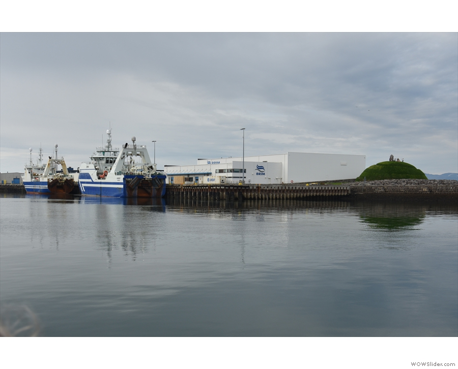 Two large trawlers tied up by a fish processing plant...