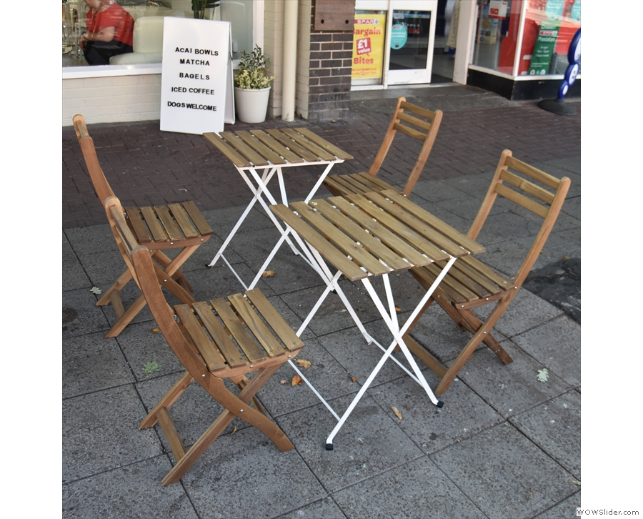 Two of the four two-person tables outside on the broad pavement.
