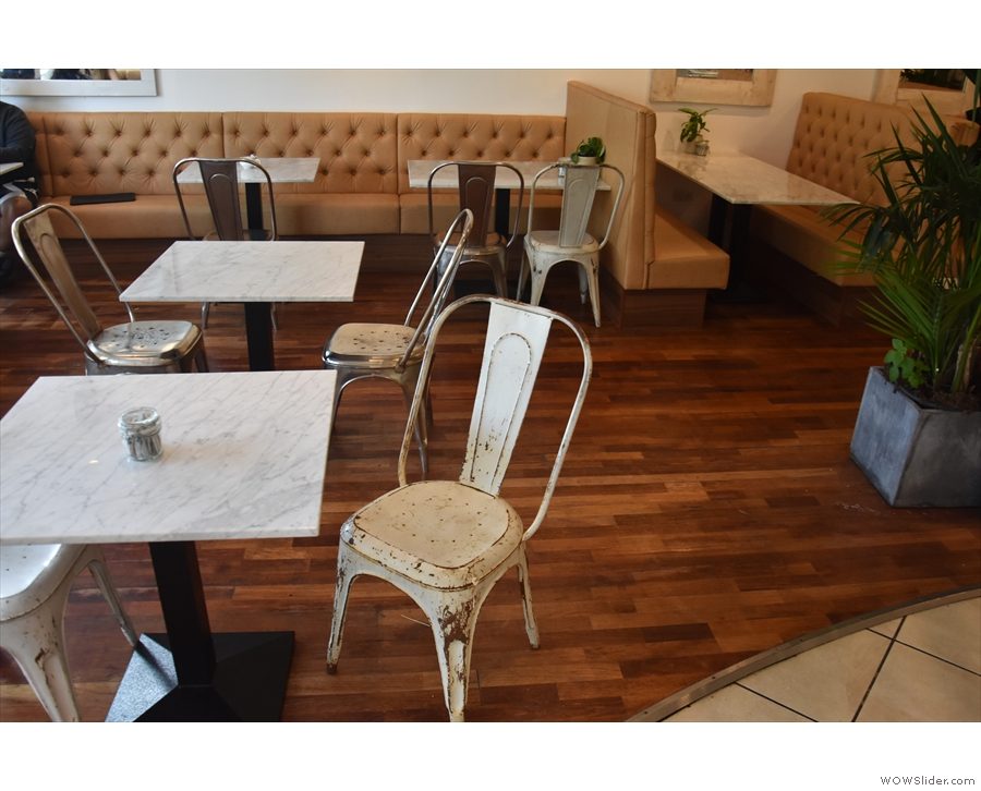 There's a pair of two-person tables between the windows and counter, with more on the...