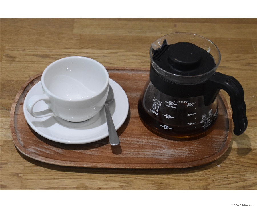The coffee is served in the carafe, presented on a tray with a proper cup.