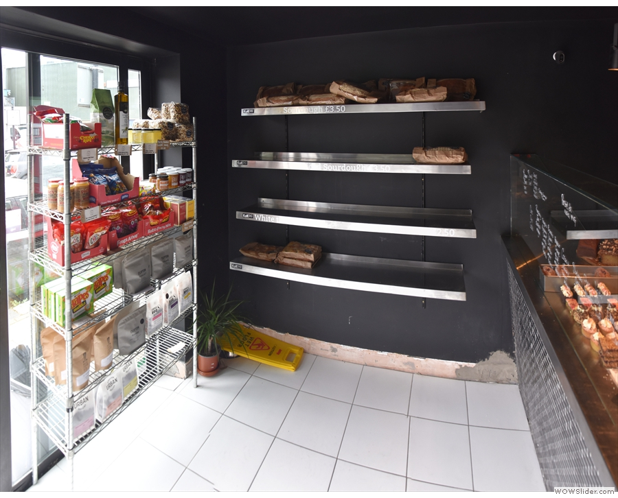 Inside, to the left of the door, is a set of retail shelves, with the bread...