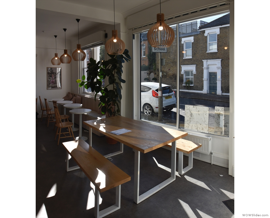 ... followed by a row of four round, two-person tables which run to the back of the space.