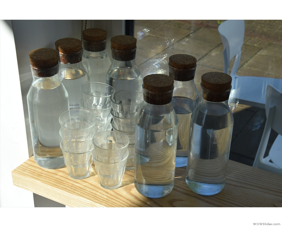 By the door is a stash of water bottles and glasses, which you can take to your table.