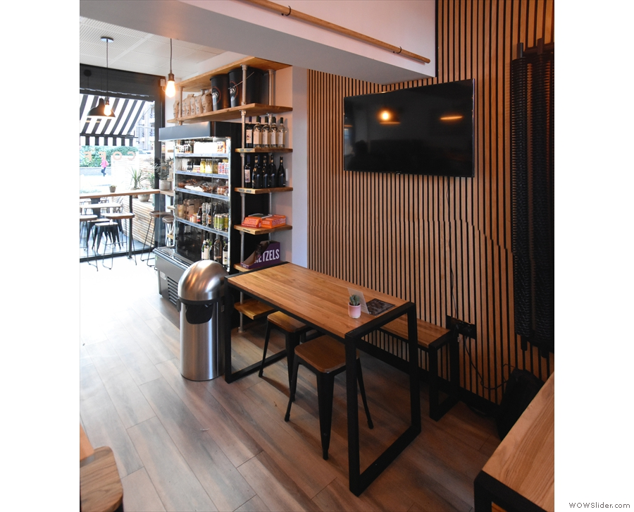On the left, just after the chiller cabinet and retail shelves, is a four-person table...
