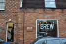 Brew, when you get there, is hard to miss with its big window sign. The door's on the left.