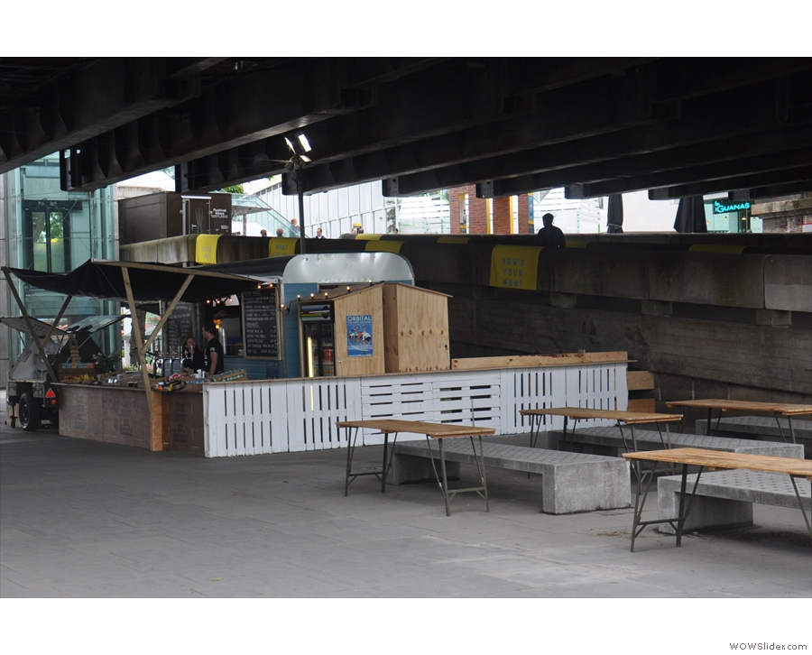 Hidden away under the Hungerford Bridge on the South Bank is a summer pop-up cafe with more than a semi-permanent look about it. It's even got tables and (concrete) benches! But who is behind it, I hear you ask...