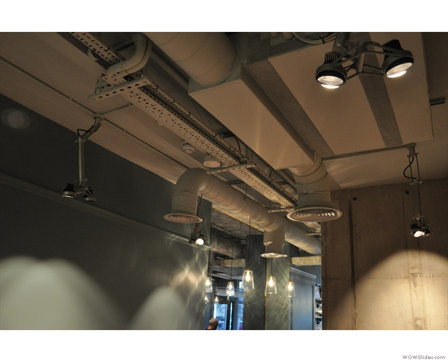 In contrast, the ceiling is modern industrial, with exposed pipework.