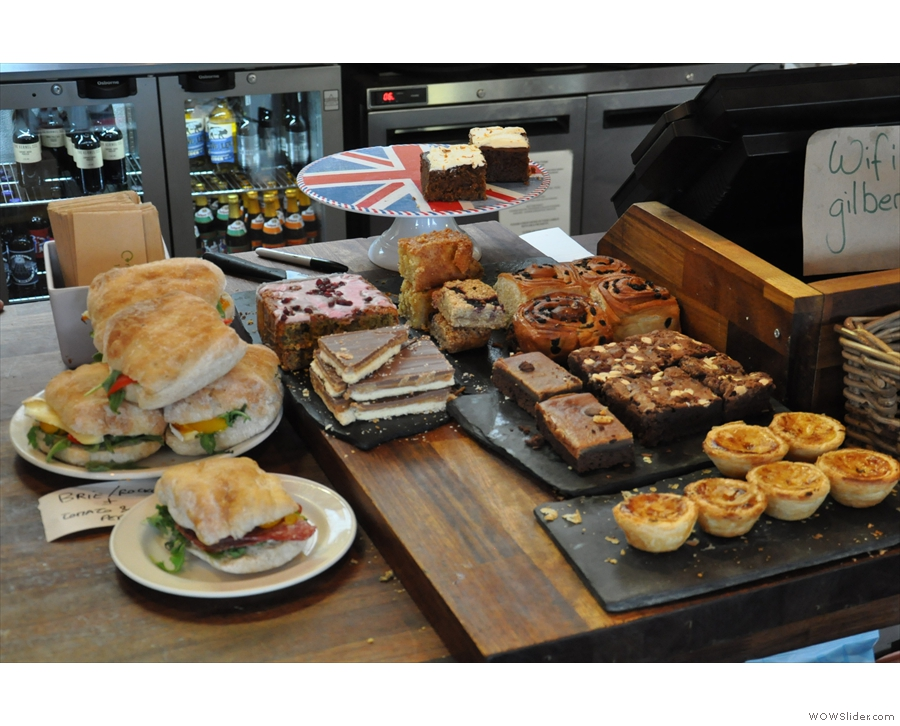 Sandwiches, plus cake, are arrayed next to the till...