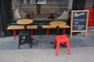 There's a couple of small tables with benches/stools on the pavement outside.