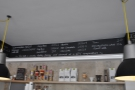 The coffee menu is written on a board above the counter.