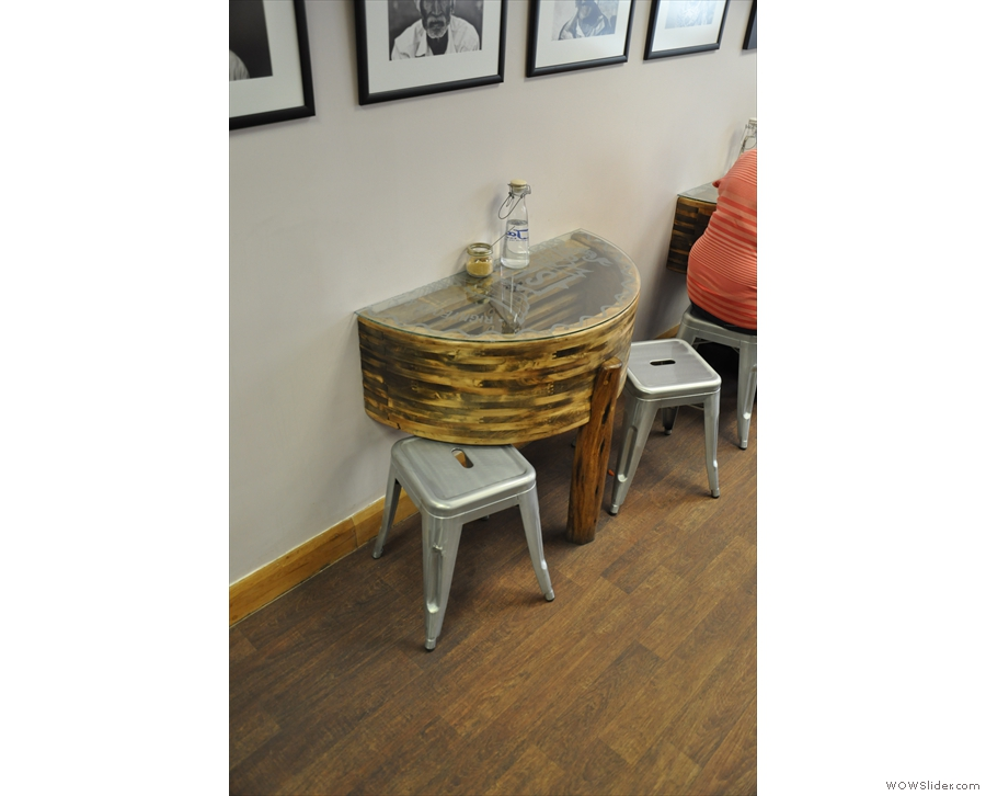 One of the two semi-circular coffee tables by the wall at the window end...