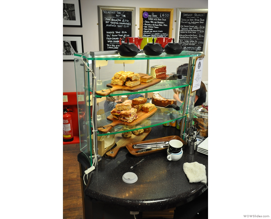 The right-hand end of the counter is laden with cakes... And tea-pots...