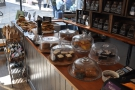 The counter with the massed ranks of sandwiches and cakes.