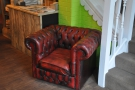 ... while its matching armchair is tucked away by the stairs on the opposite side.
