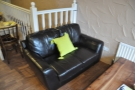One of the pair of black leather sofas in close up.
