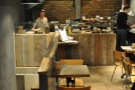 The counter's at the back, with a row of two-seater tables on the right & stairs on the left.