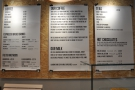 The menus hang on the wall behind the counter.
