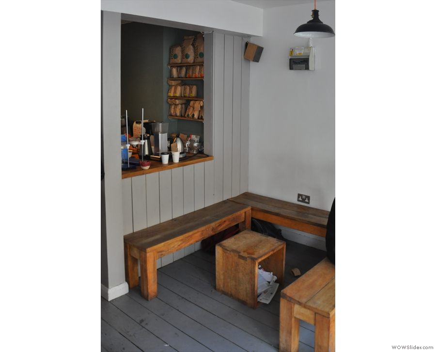 It consists of two bays of wooden benches, one in the window, the other by the counter.