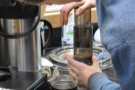 Once the timer goes off, Adam presses down on the Aeropress to complete the extraction.