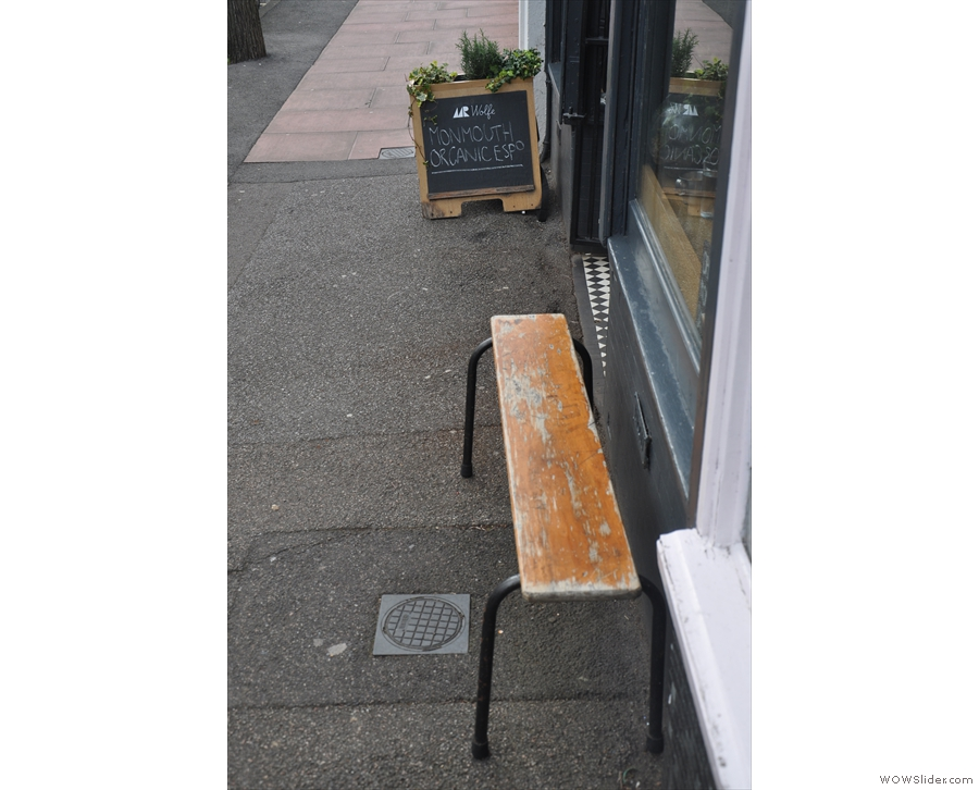 There's a bench outside, the quiet street making it a realistic seating option.