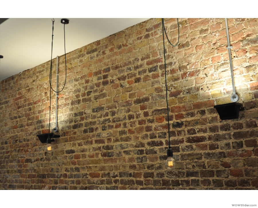 There are plenty of lights, both bare light-bulbs and uplights on the walls.