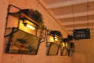 Back upstairs, and angled mirrors line the wall opposite the counter, hanging above the bar.
