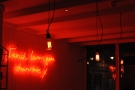Light-bulbs and neon signs on the wall.