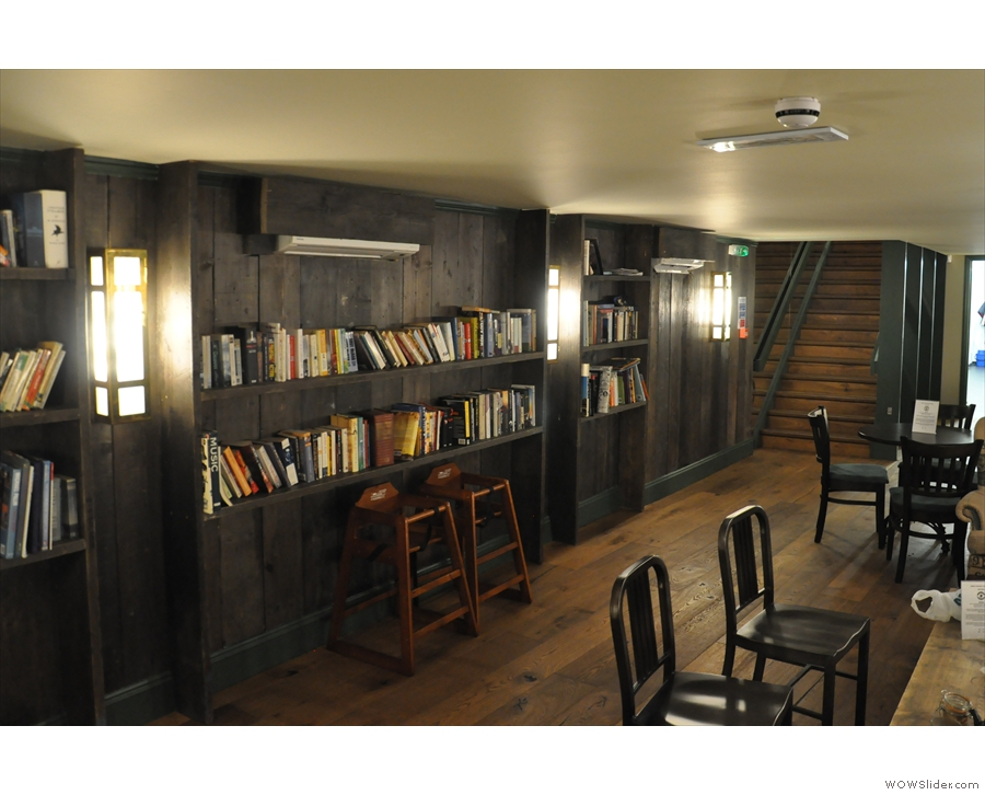 The seating is all on one side, while against the opposite wall are some bookshelves.