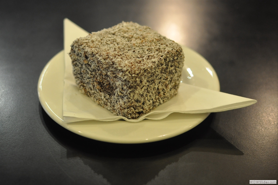 ... and a cube of cake! It's a Lamington, a vanilla sponge rolled in dark chocolate and coconut.