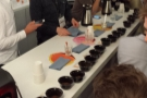 To the cupping. First the cupping bowls are put out and filled with coarse ground coffee...