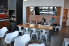 Beyond them is a communal table and a row of small, round tables at the back...