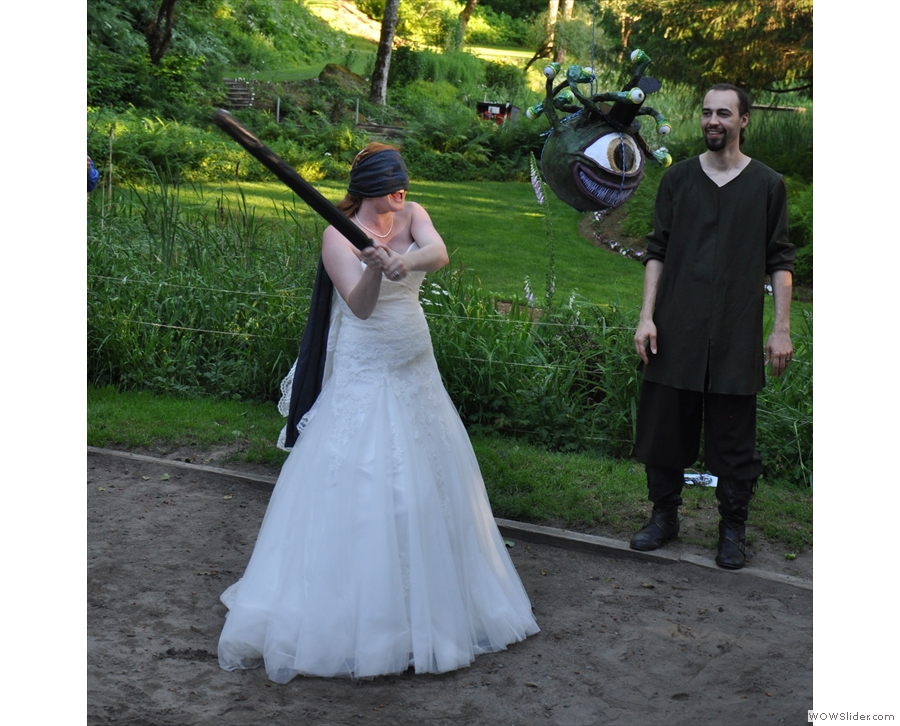 I see... Well, more than Elisa does! The idea's to hit the piñata with the bat. While blindfold.