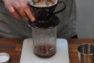 I've seen a few baristas give the coffee a stir at the this point. Helps wet the beans...