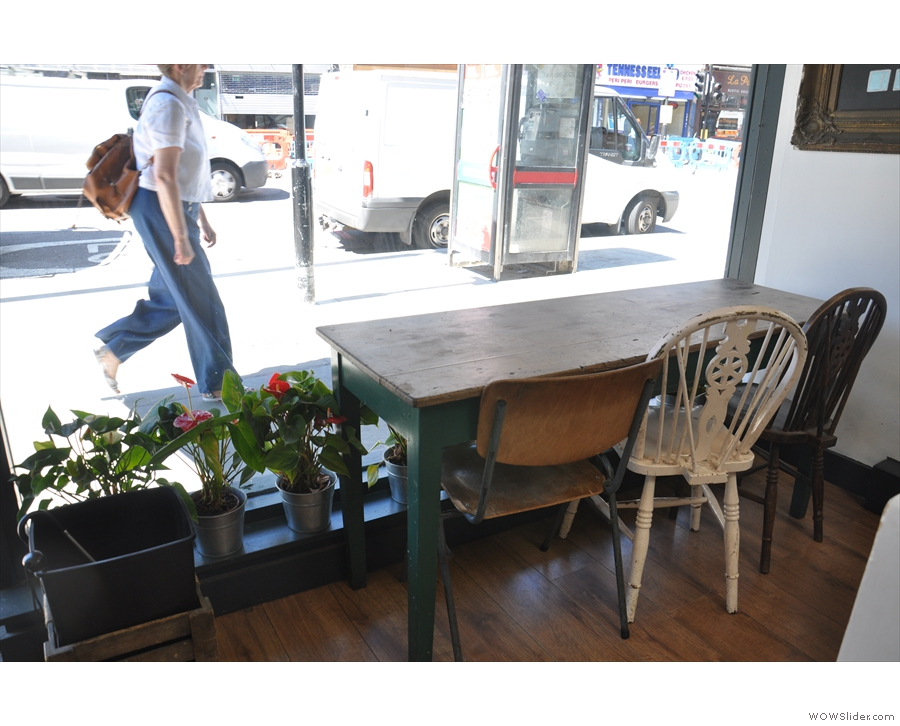 The window table, complete with pot-plants, is good for people watching on the busy street.