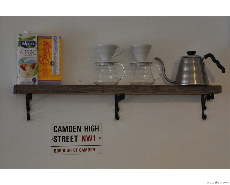 The V60s and the pouring kettle on a shelf next to the coffee menu.