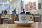 My sharply in-focus espresso watches a (very) blurry Andy at work.