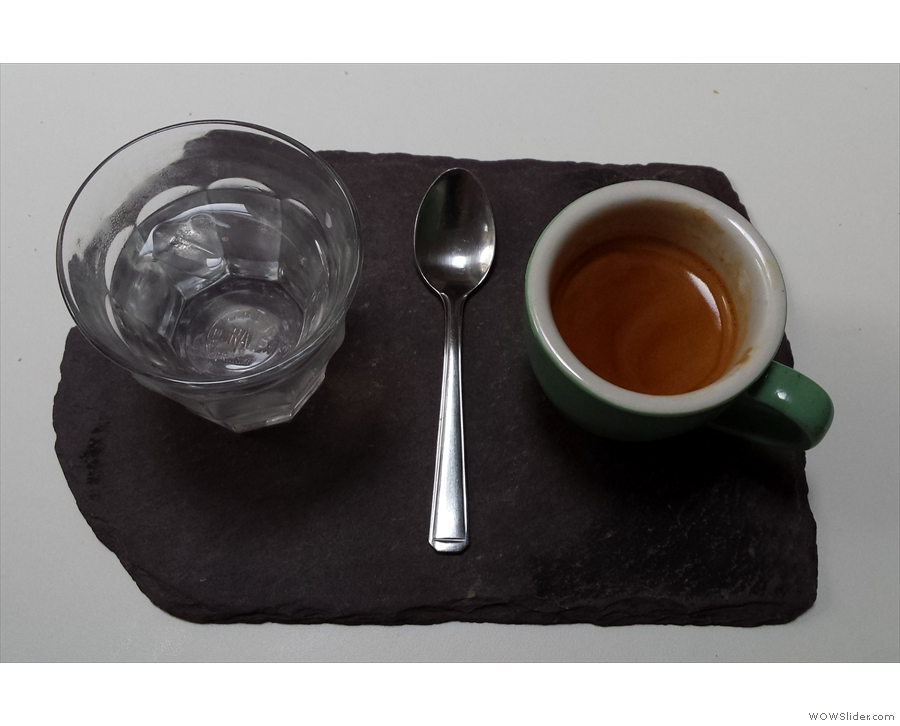 Espresso on a slate. With a glass of water, naturally.