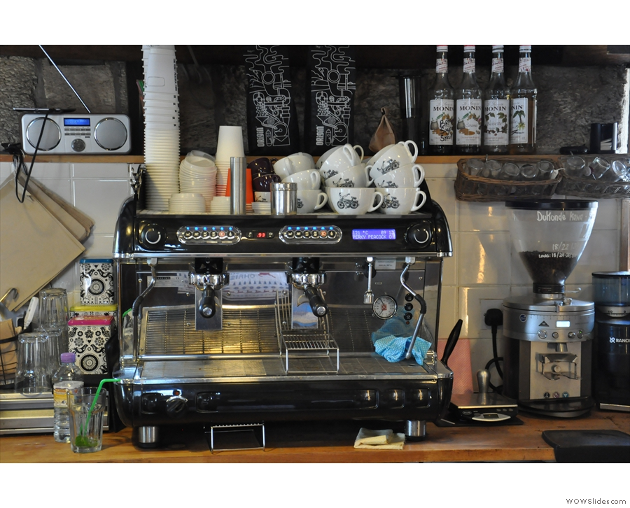 The espresso machine is behind the counter, business end facing the customers.