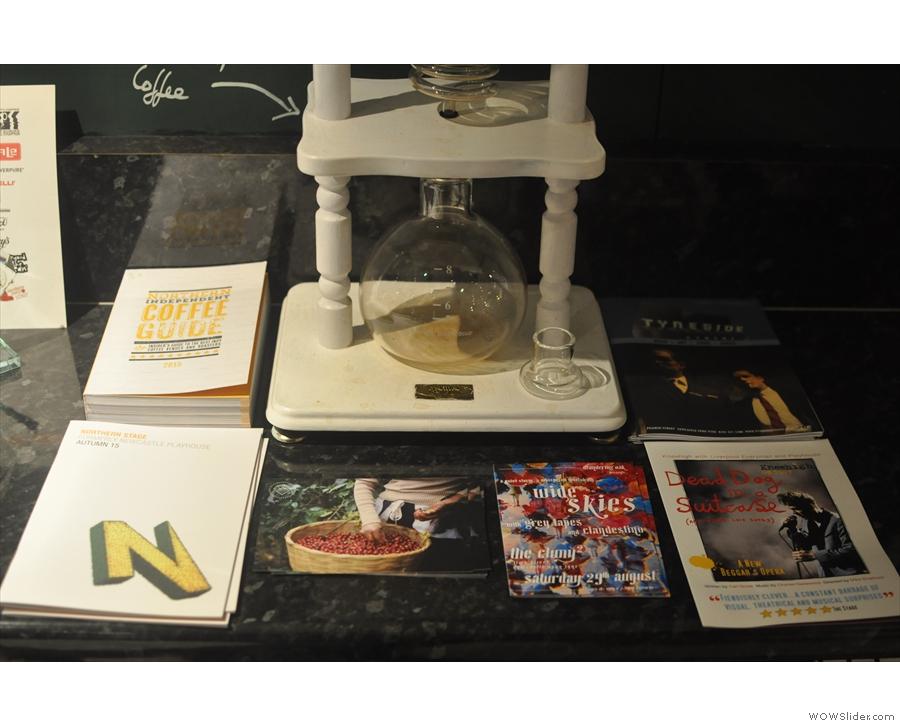 Magazine/book display around the base of the cold-brew aparatus.